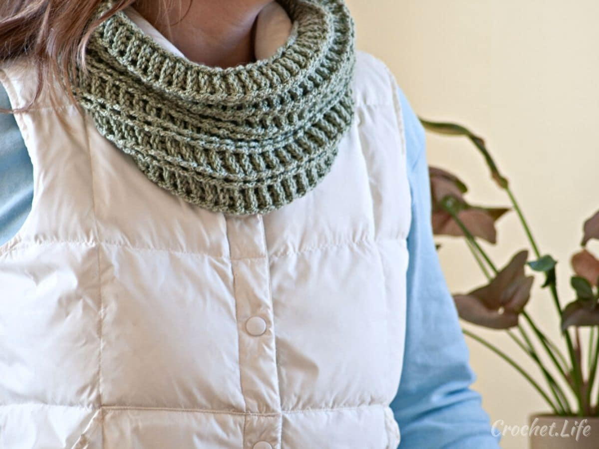 Woman wearing blue shirt and white vest with crochet green cowl