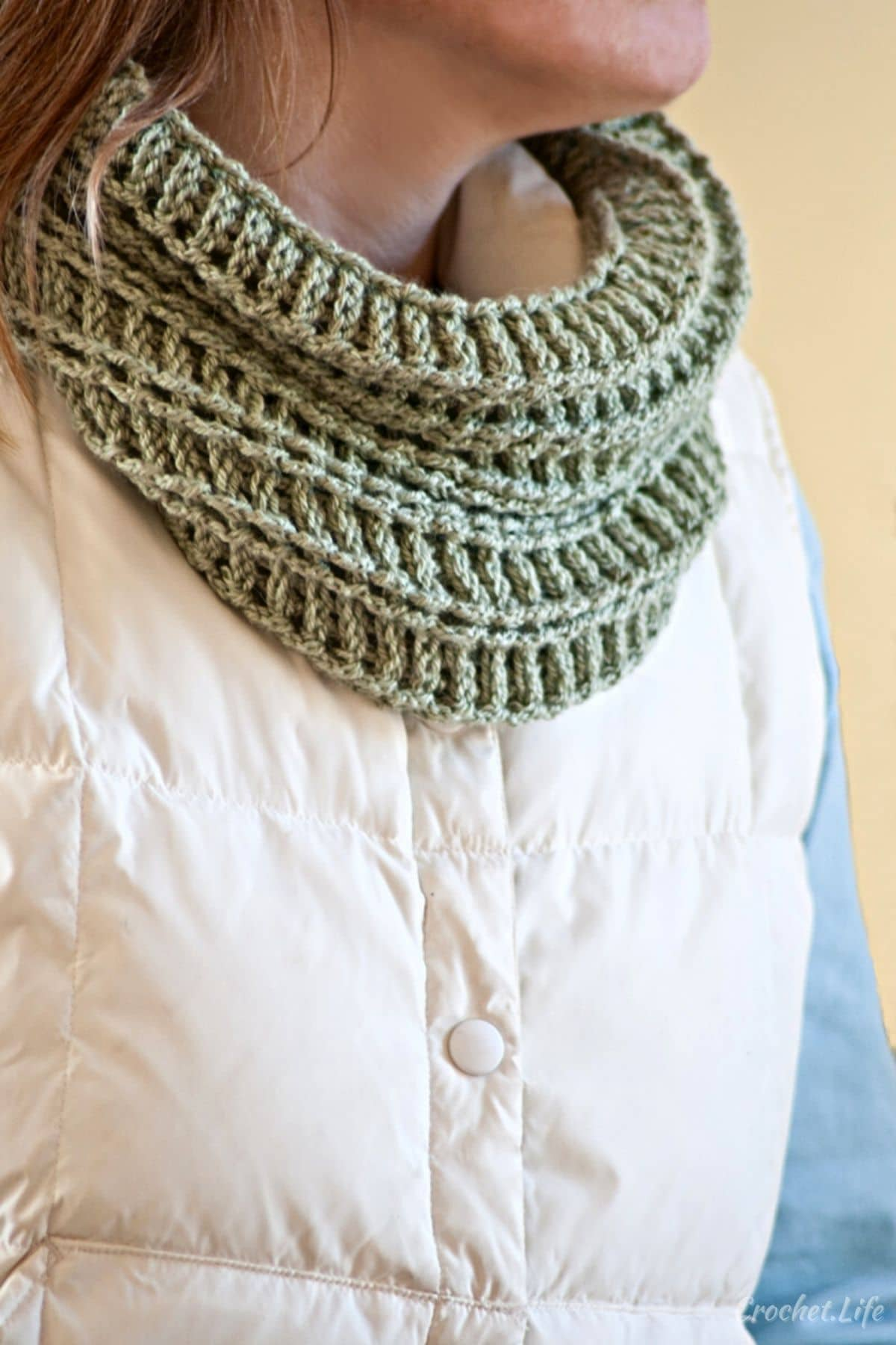 Woman in white puffer coat with crochet green cowl