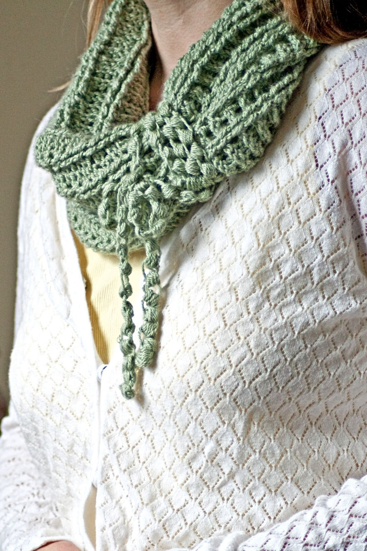 Woman wearing white sweater over yellow shirt with light green cowl and fringe