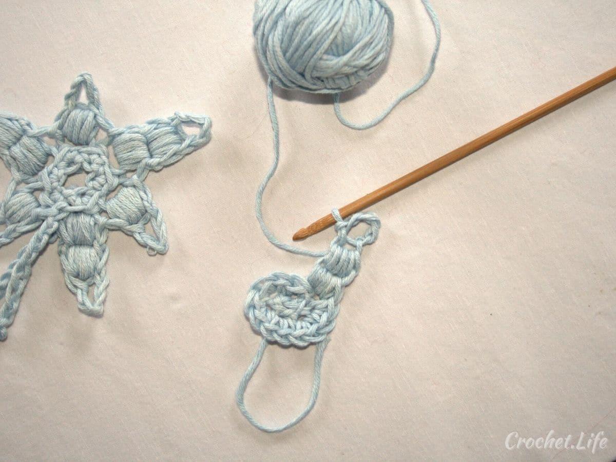Light blue yarn on crochet hook next to crochet snowflake