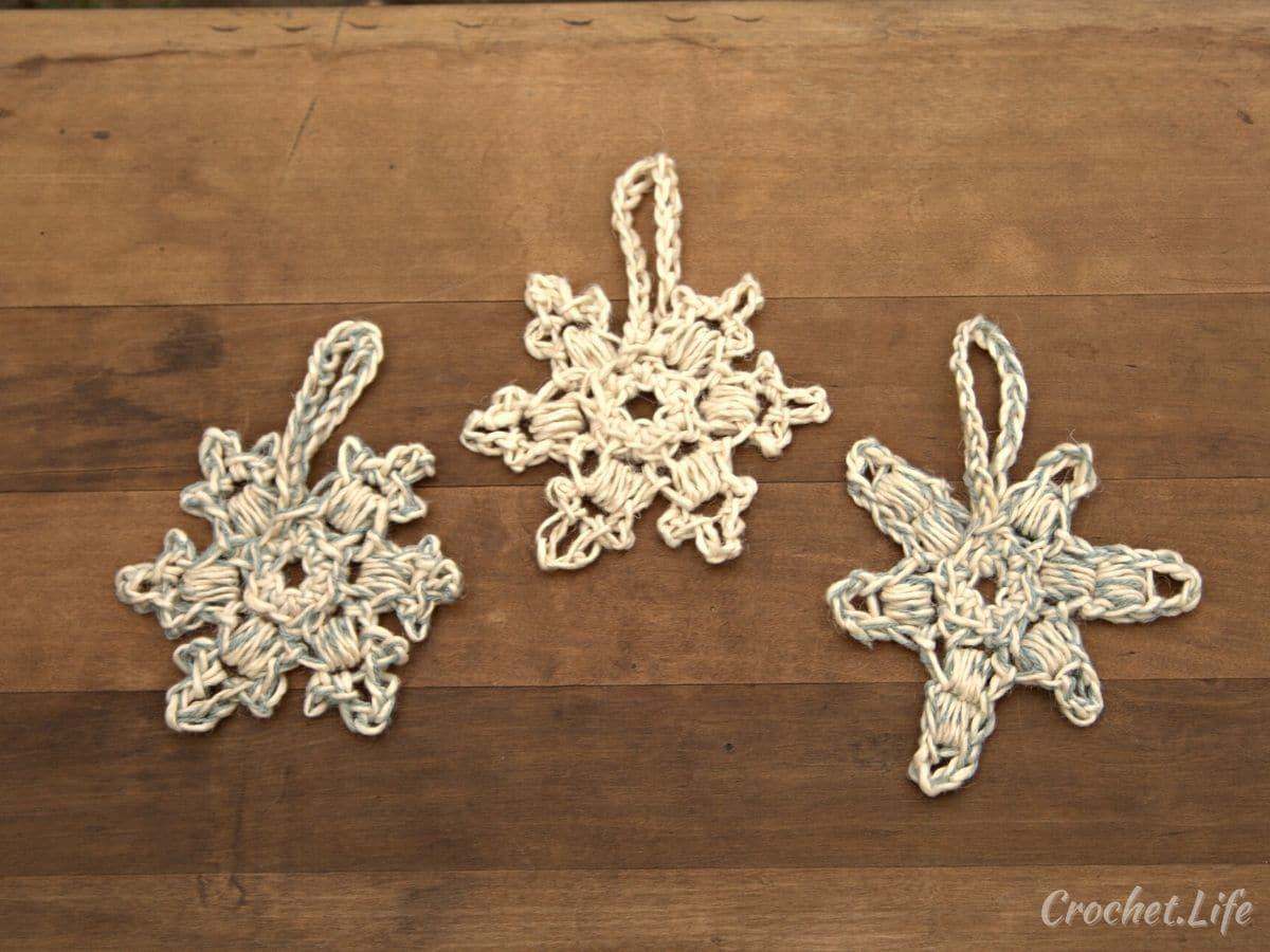 Three white crochet snowflakes on wood