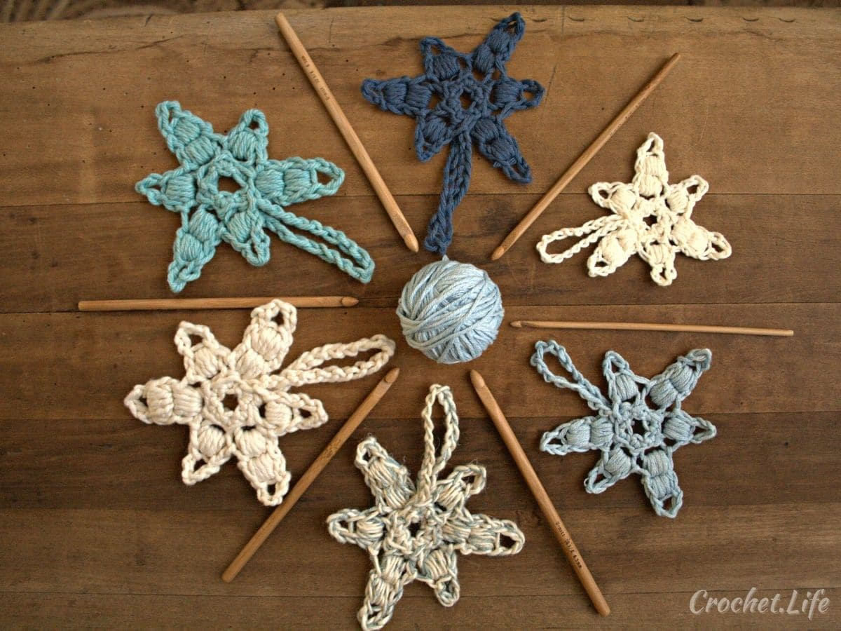 Crochet blue snowflakes laying in a circle around crochet hooks and ball of yarn