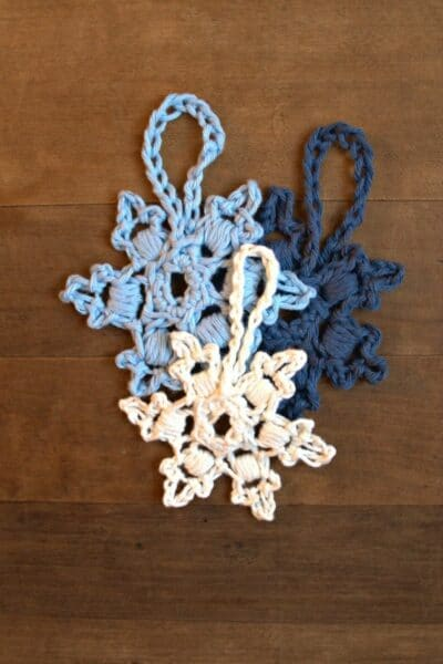 Blue and white crochet snowflakes stacked together on dark wood table