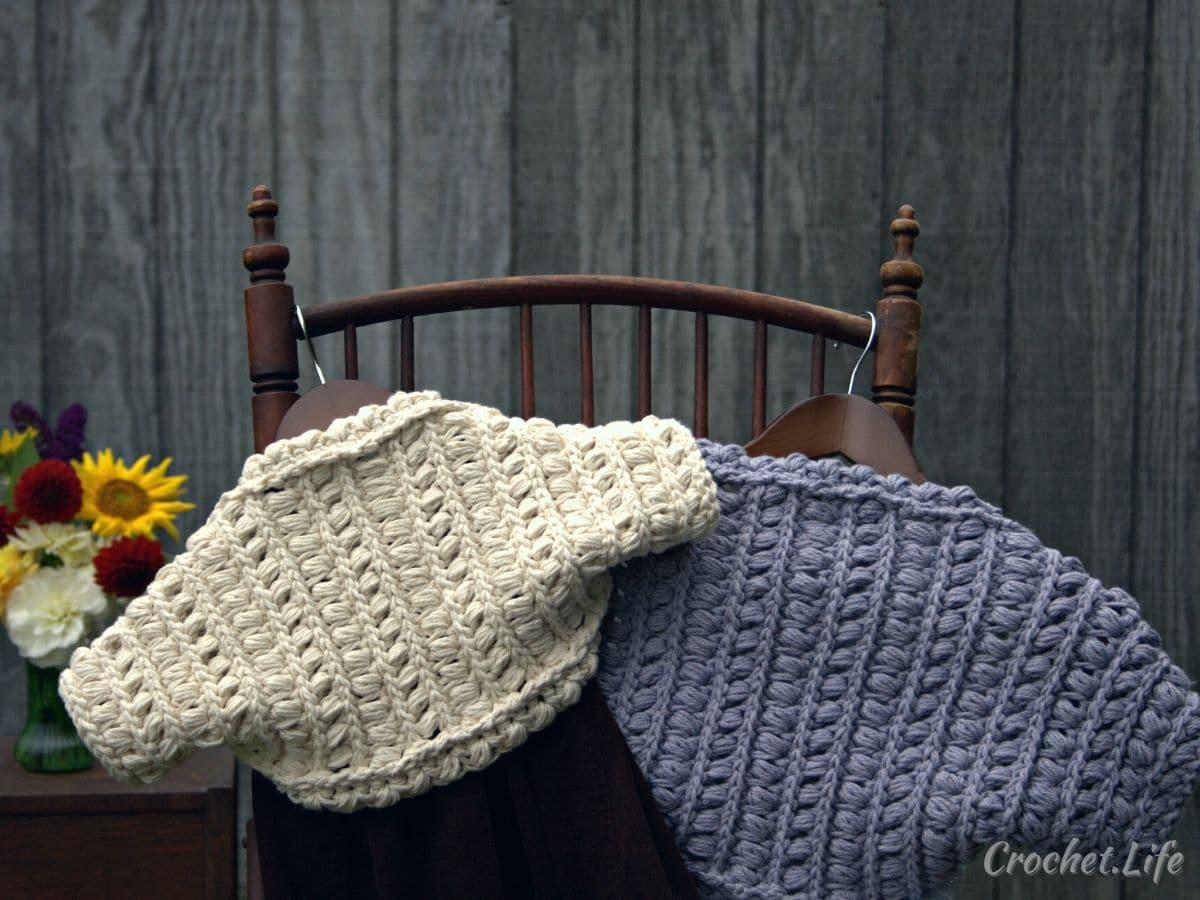White and gray shrugs hanging on a wooden chair by gray wall