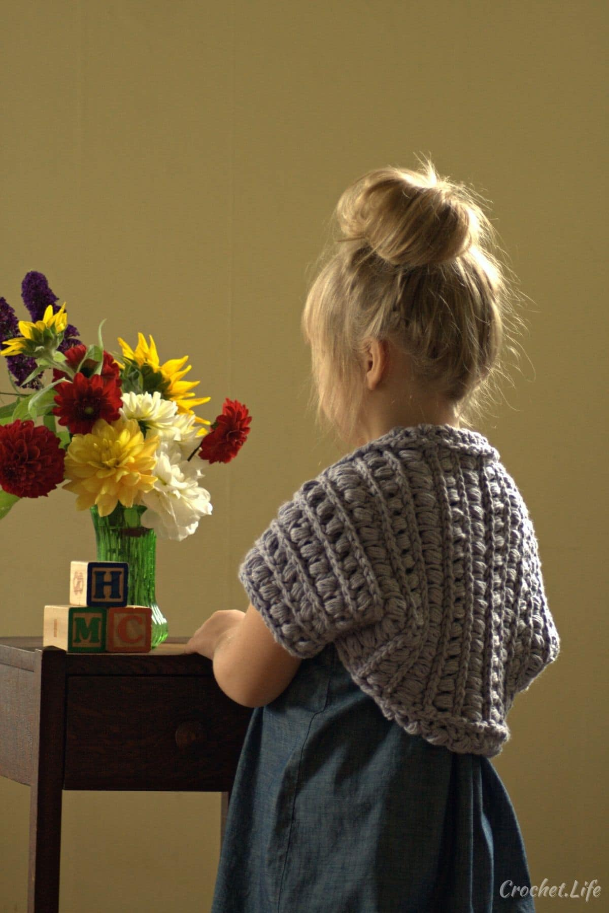Blonde little girl in blue dress with gray shrug by table with flowers