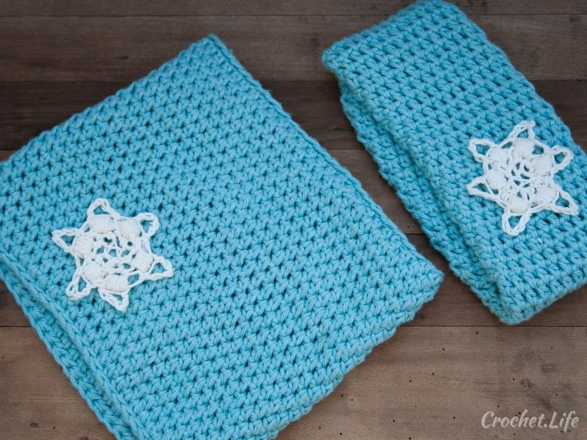 Crochet teal cowl and headband with white snowflake motif on wood table