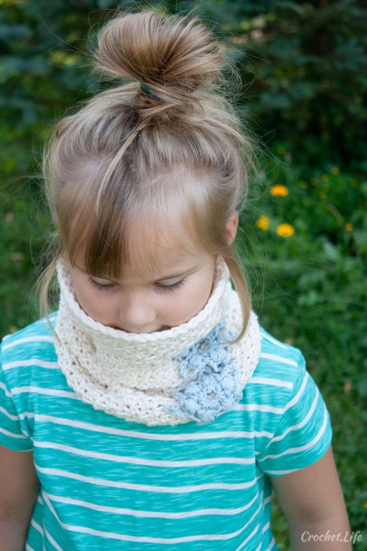 Little girl wearing teal striped shirt wearing white cowl with blue snowflakes