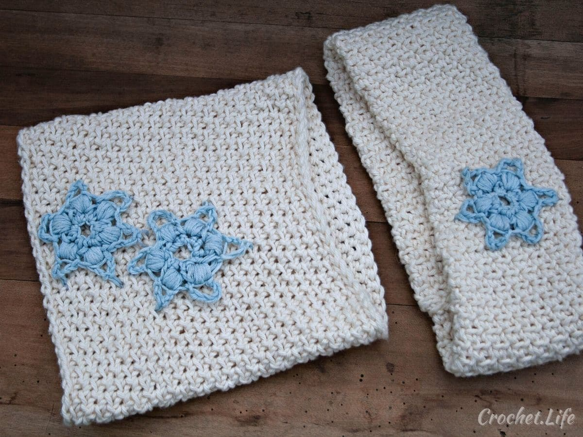 Crochet white cowl and ear warmer with blue snowflakes laying on wood