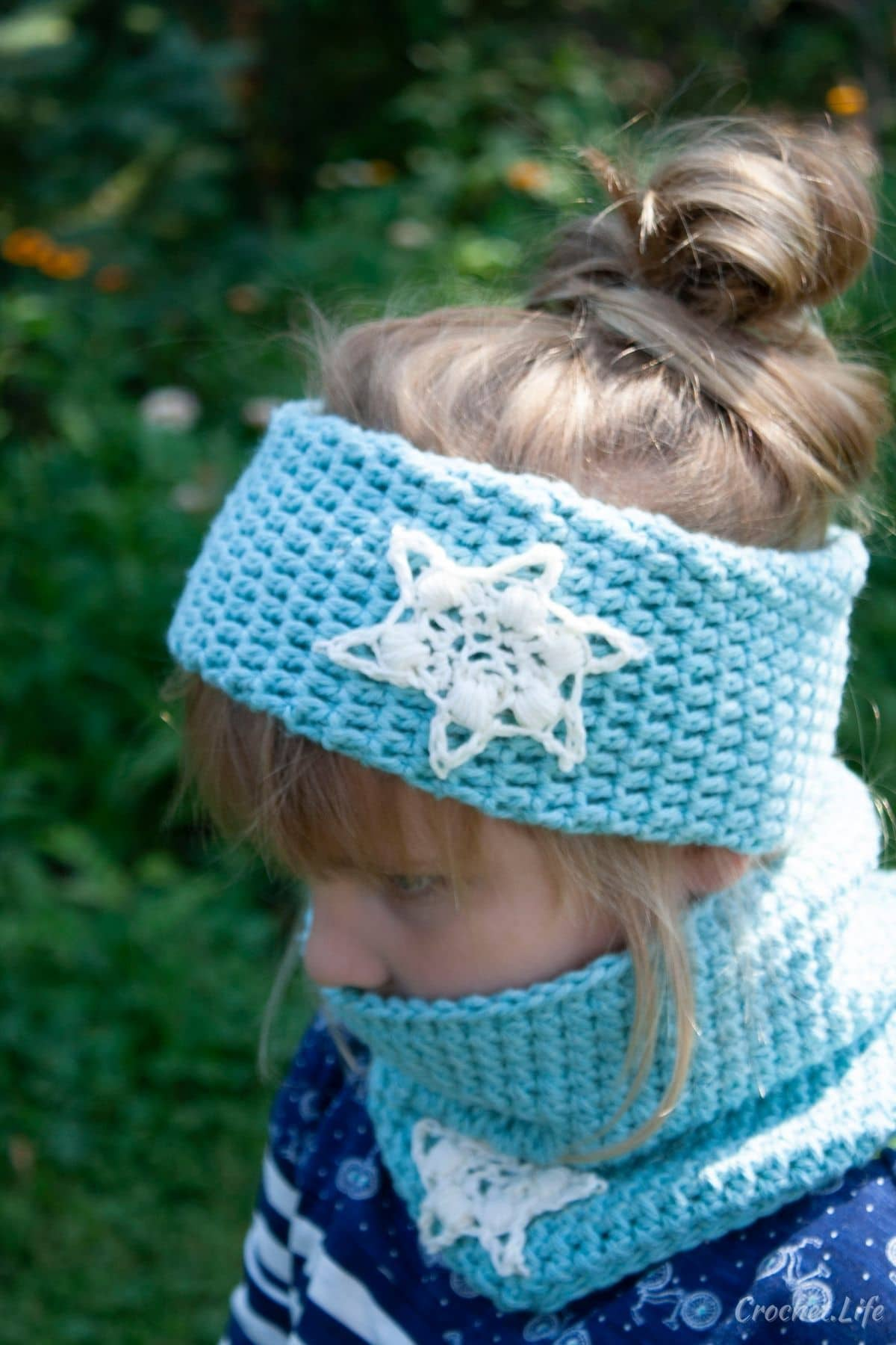 Blonde girl in blue shirt wearing light blue cowl and matching headband with white snowflakes