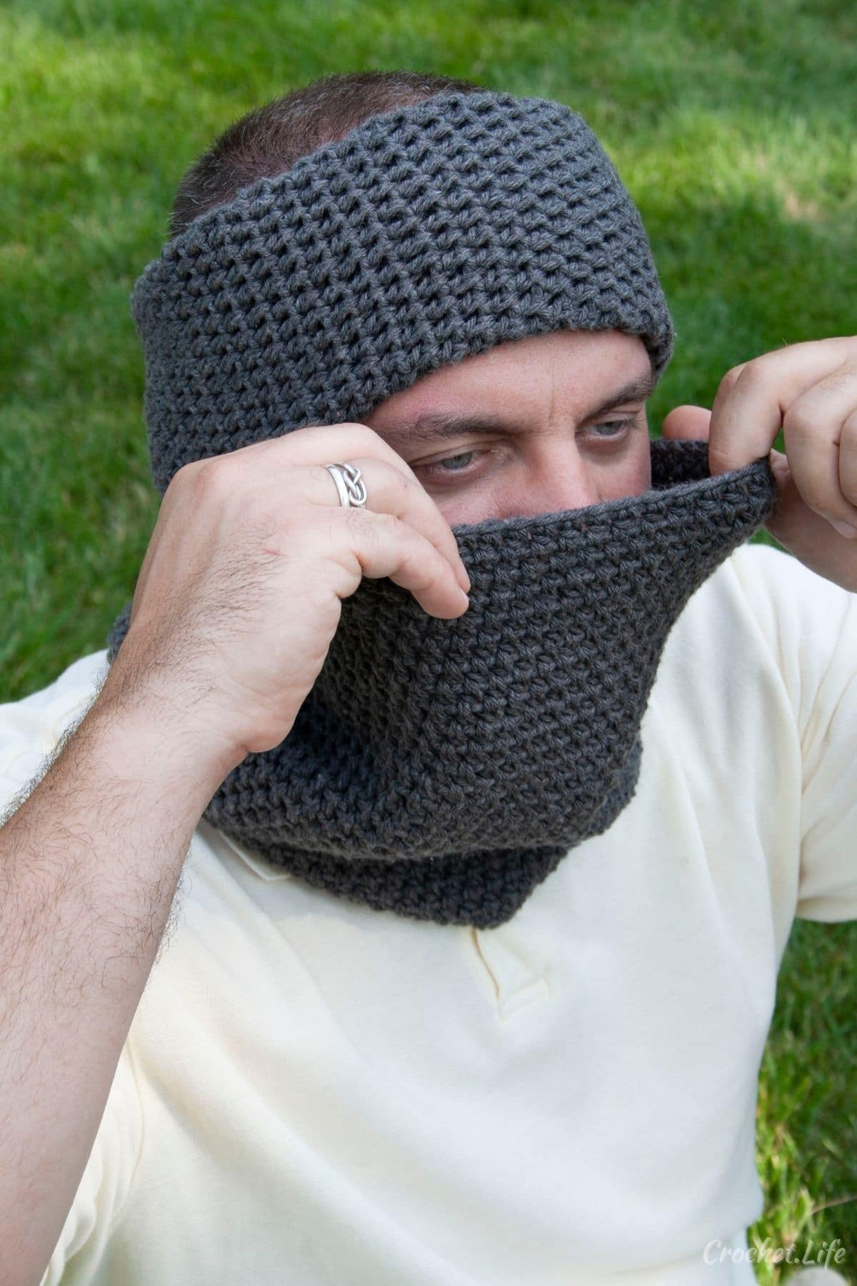 Man wearing white shirt with dark gray cowl and headband