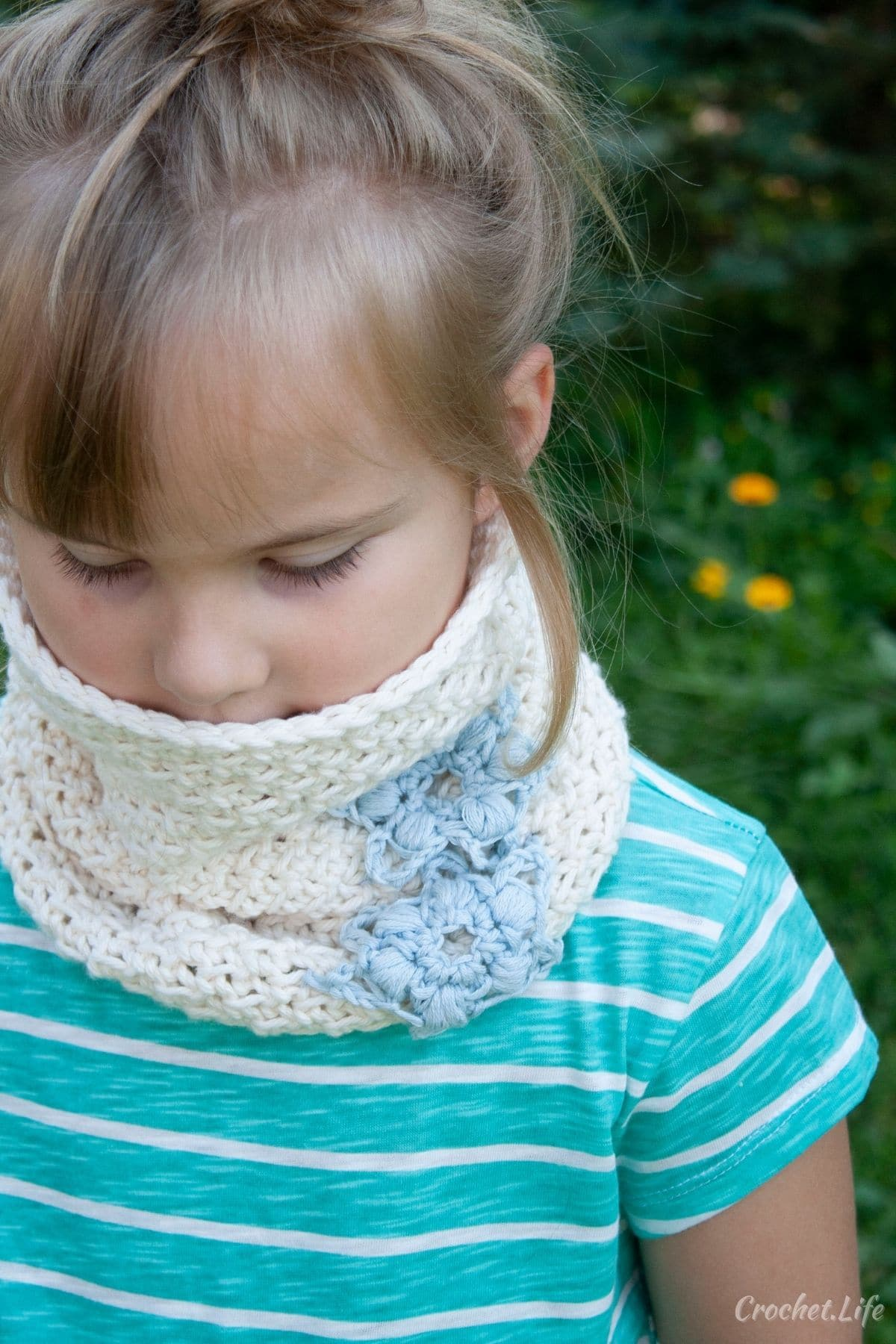 Crochet white cowl with blue snowflake on little girl in blue