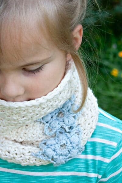 Girl in teal striped shirt wearing crocheted white and blue cowl