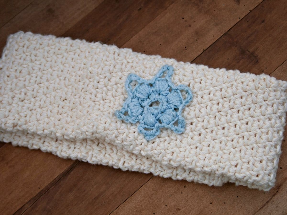 Crochet white headband with blue star on wood table