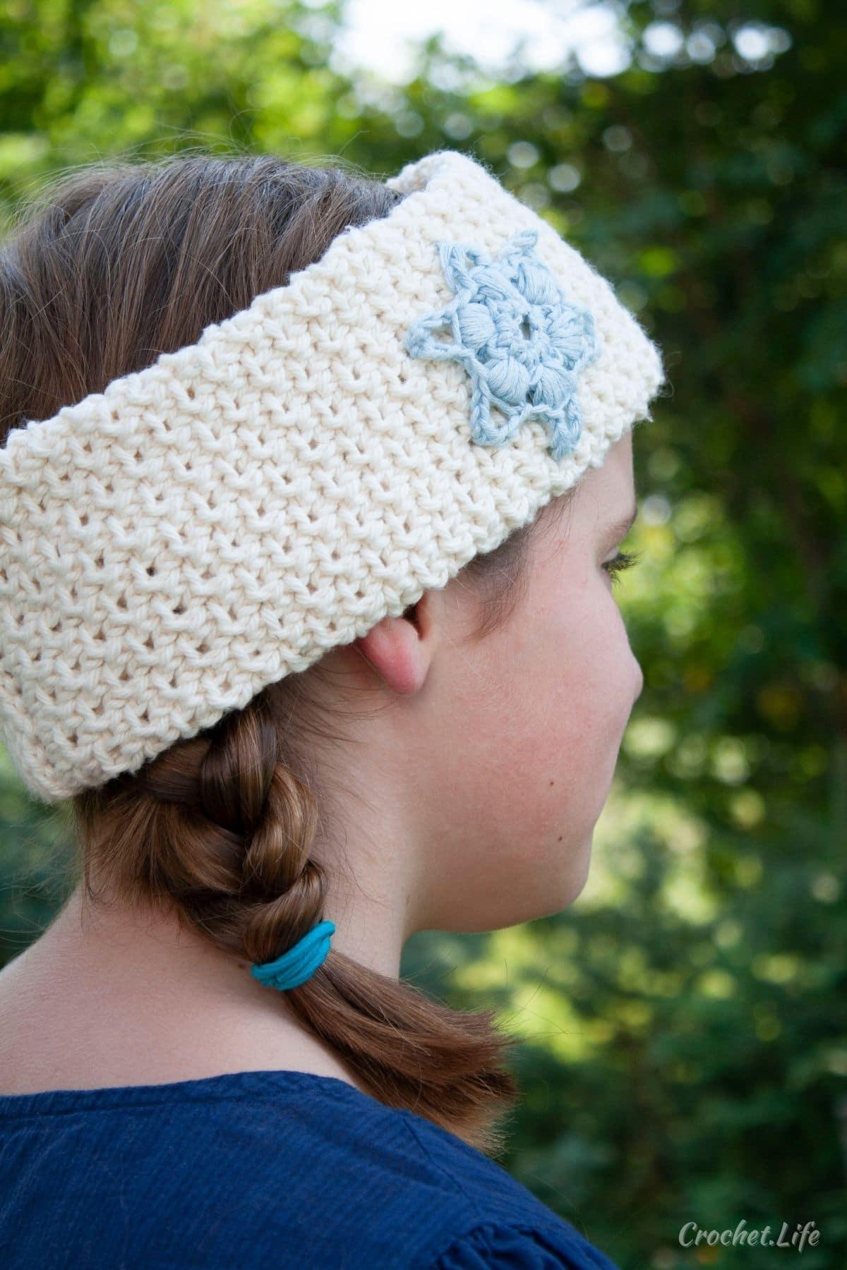 Girl in blue shirt with brown hair in braids facing away wearing white crochet headband