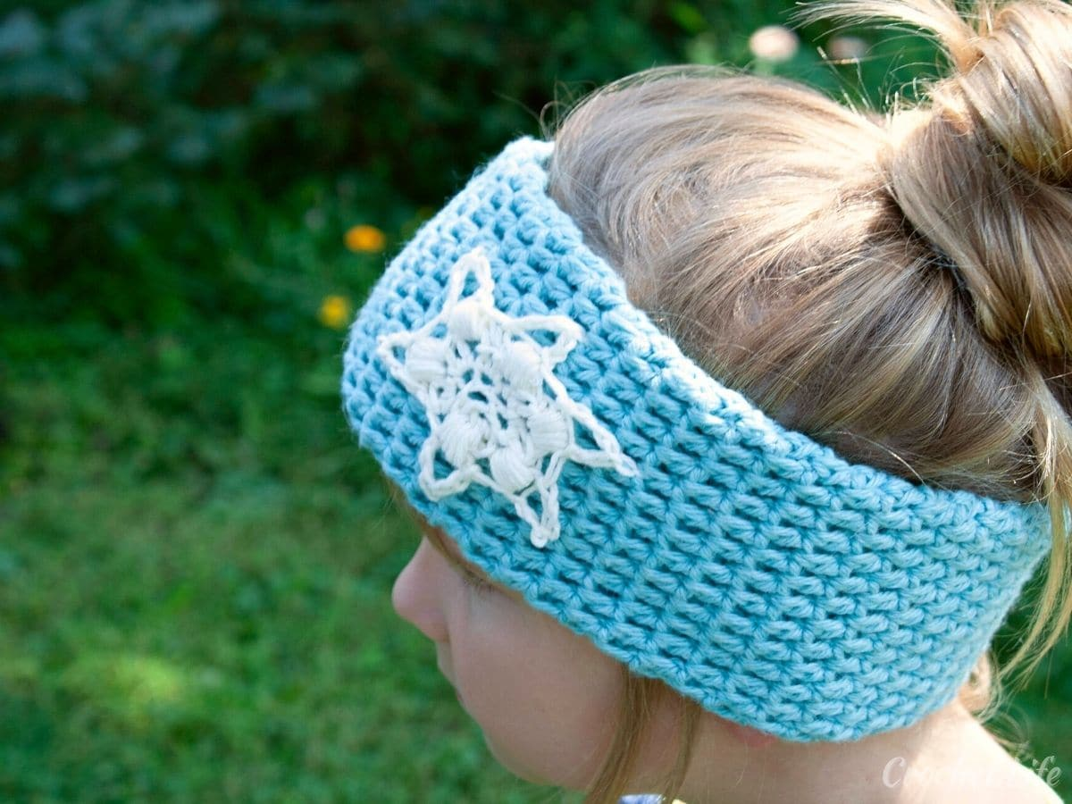 Blonde girl wearing blue headband with white snowflake on side