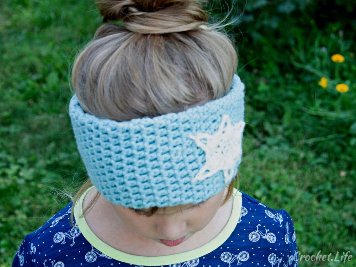 Little girl wearing blue shirt looking down to show blue crochet headband with snowflake