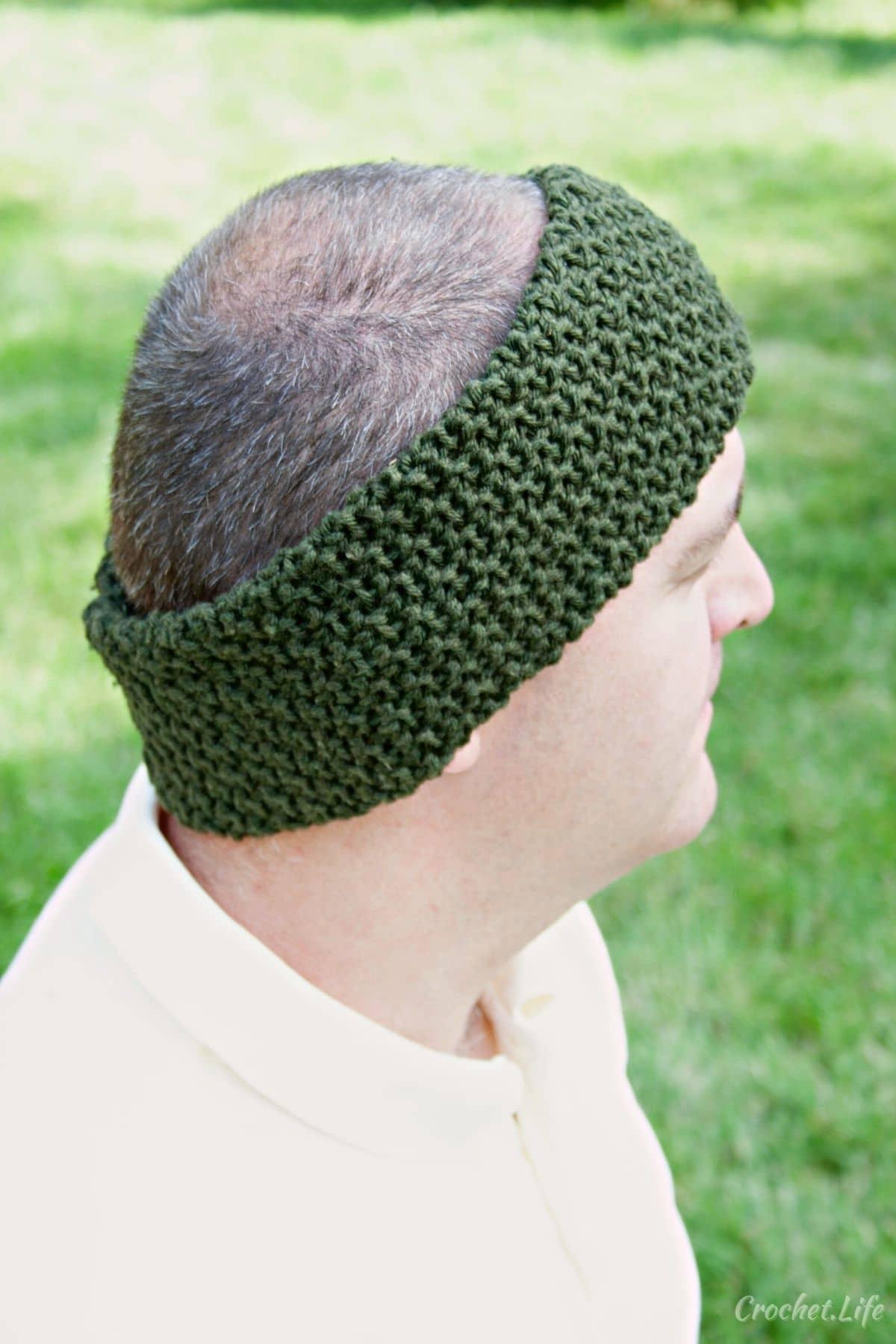 Man in white shirt wearing green crochet headband