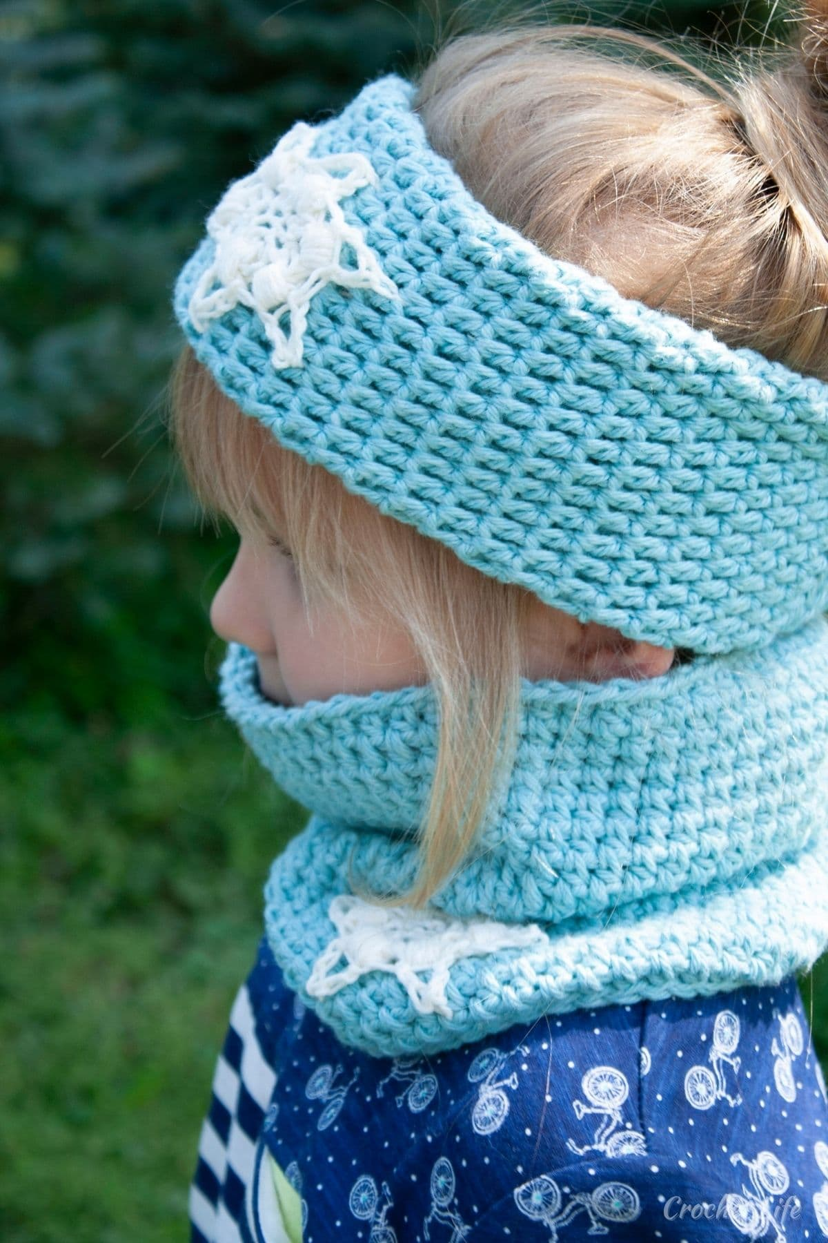 Small blonde girl in blue shirt looking away wearing blue headband and cowl