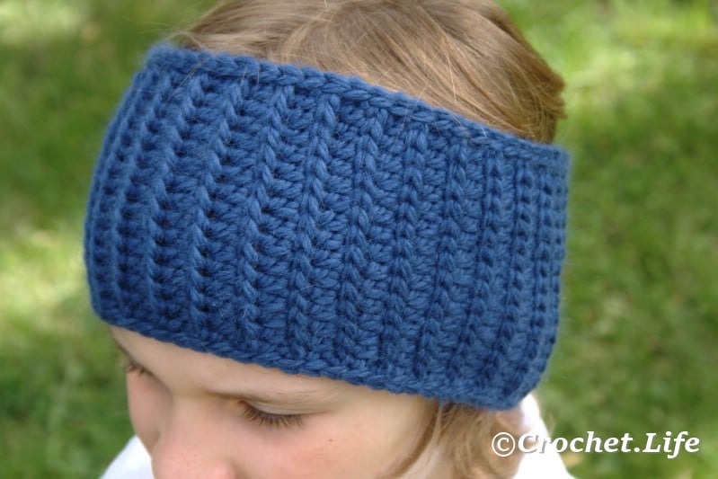 Simple blue headband worn by a blonde girl, made out of this pattern.