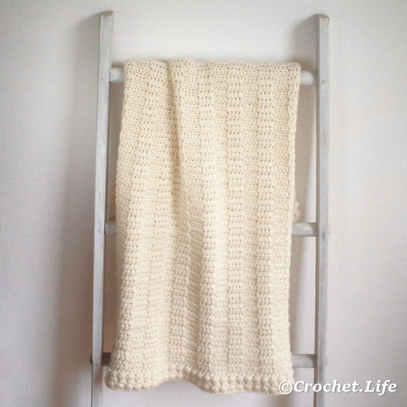 Finished crochet blanket shown on a ladder.