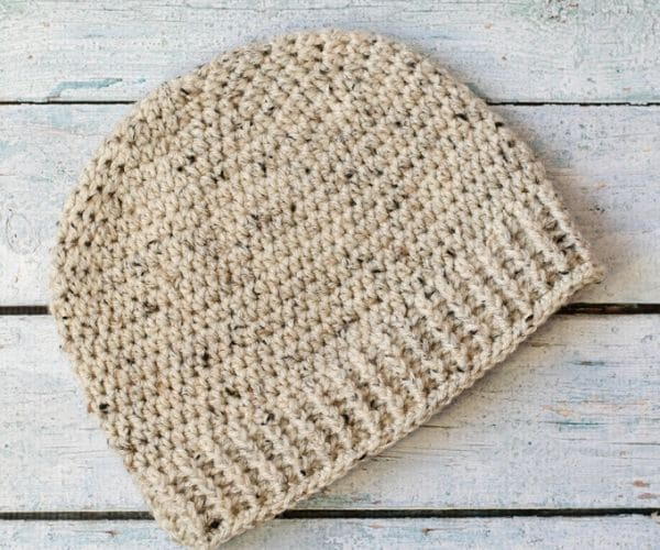 Ivory mens beanie on a wooden surface