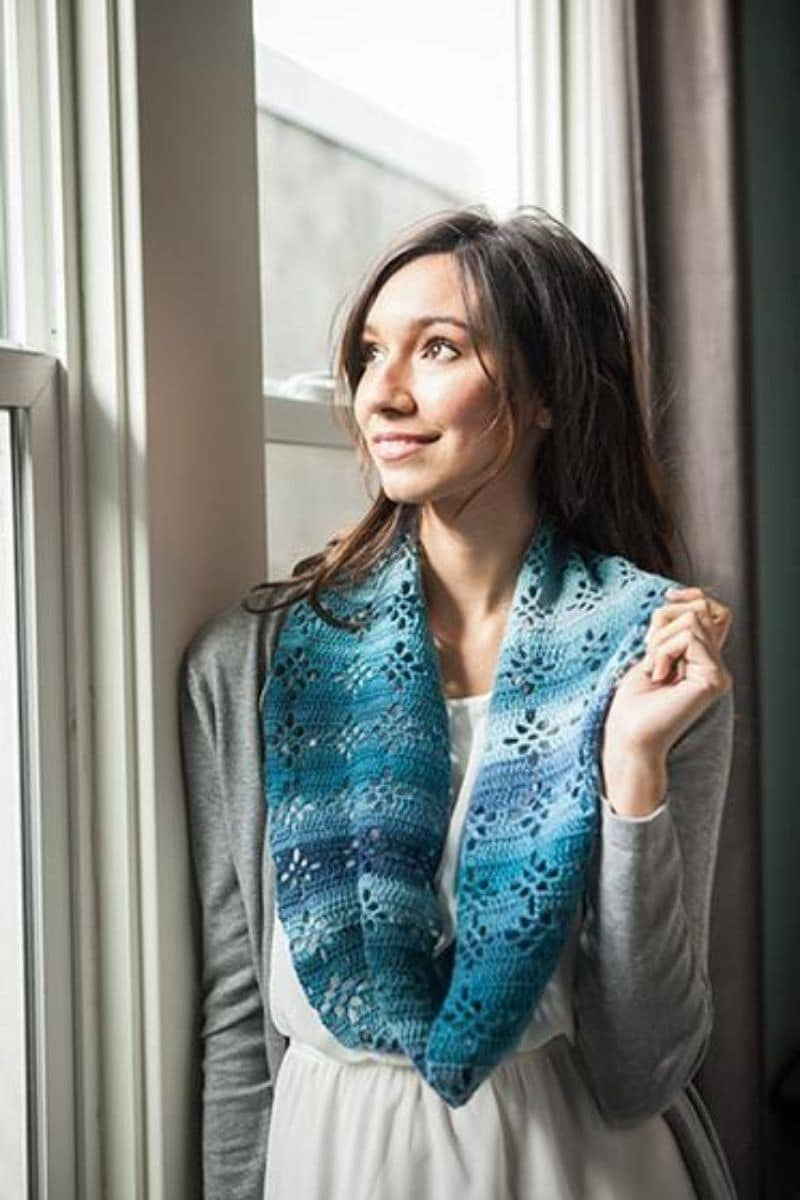 Brunette at window in teal striped scarf