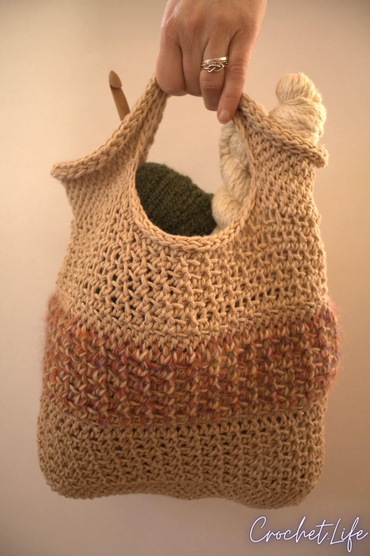 Hand holding crochet bag