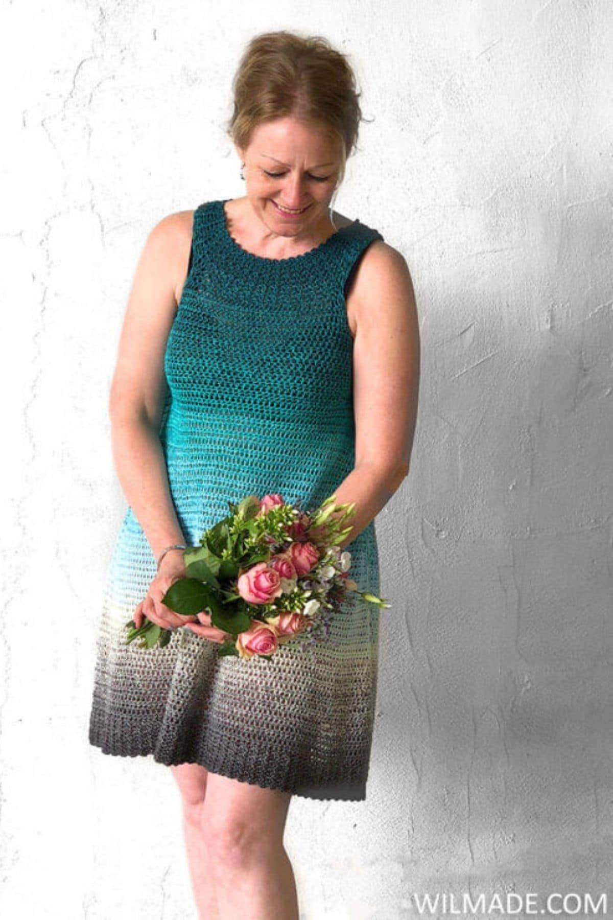 Woman in teal ombre tank dress holding flowers
