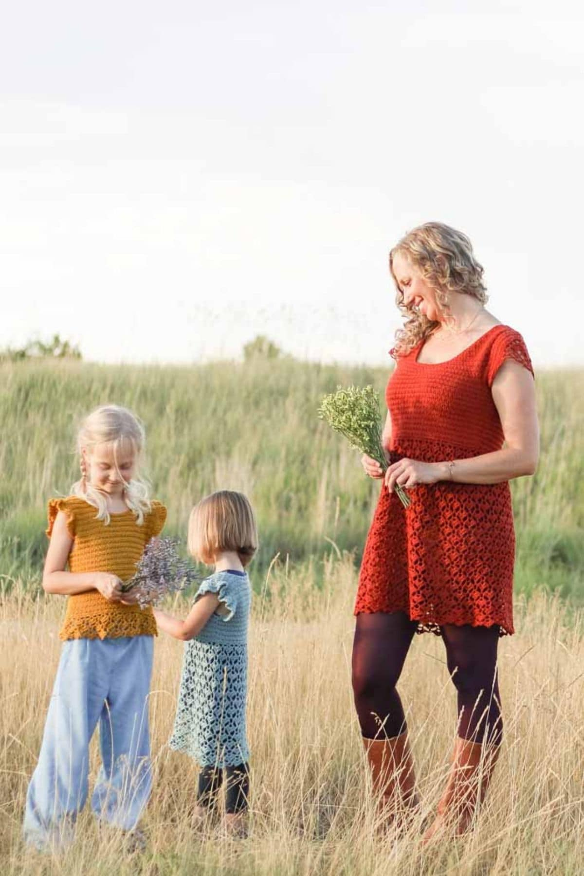 Woman in maroon dress next to two girls in dresses