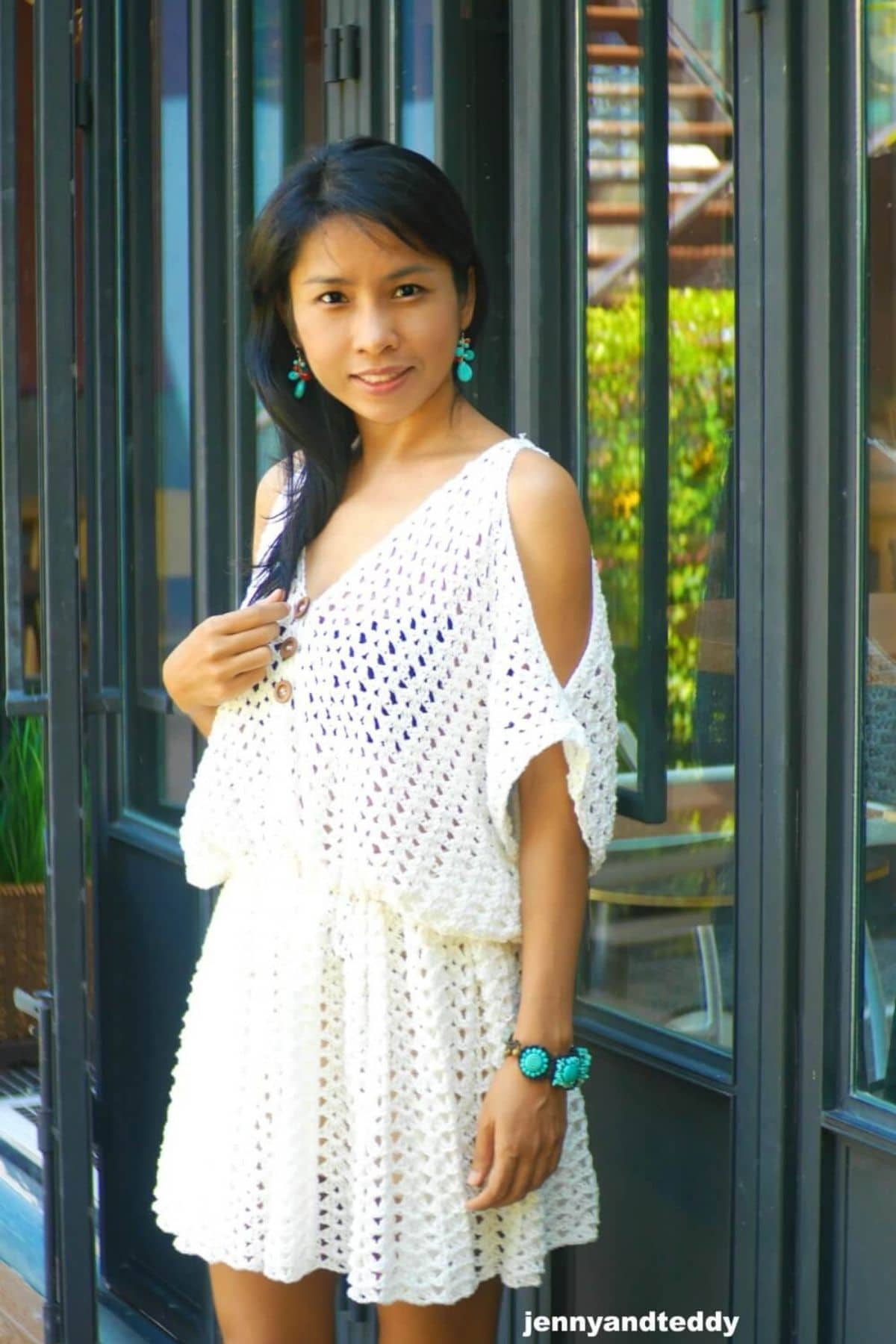 Woman wearing white boho dress against fence