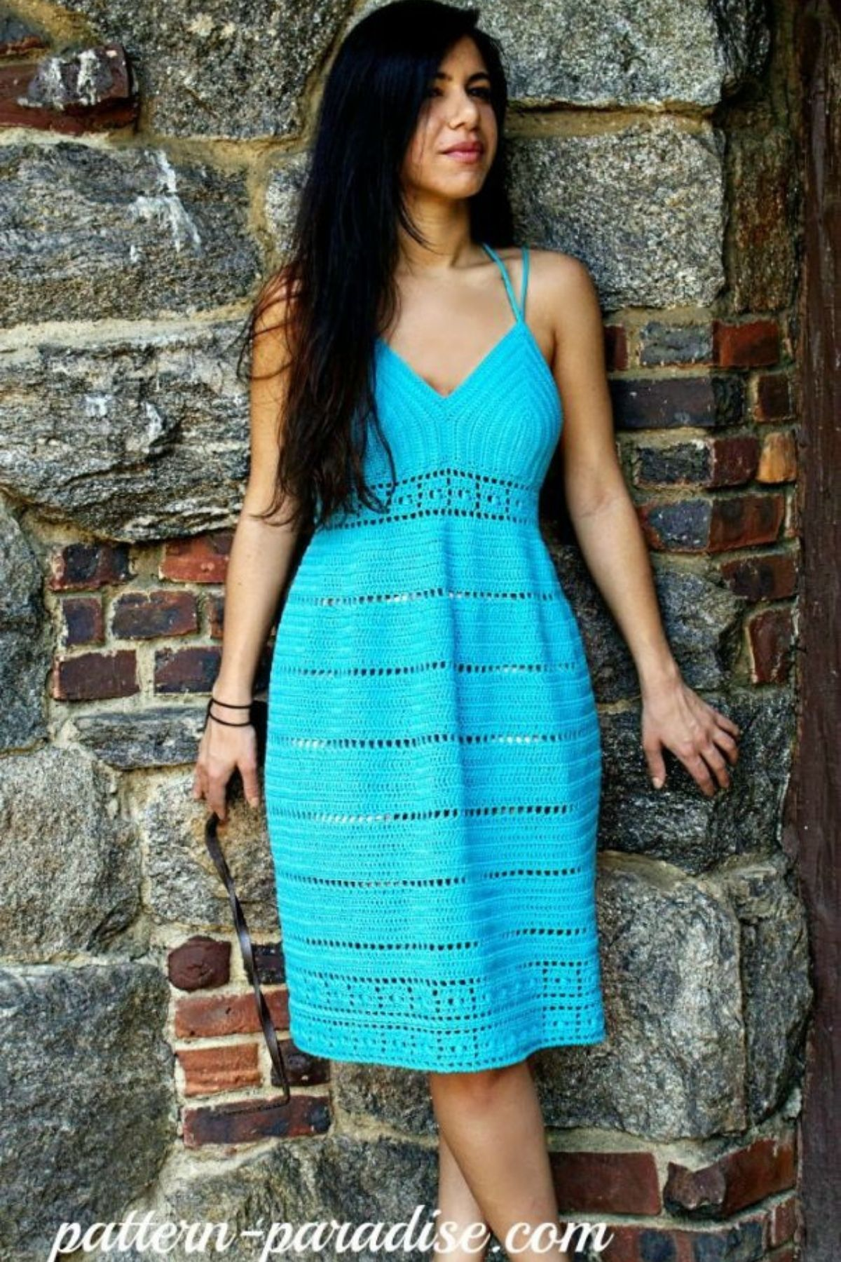 Brunette in teal dress against brick wall