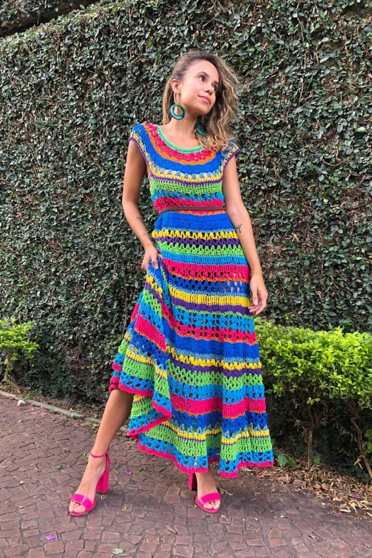 Woman in striped rainbow dress by shrubs