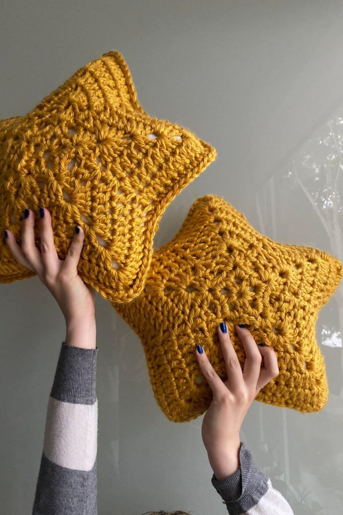 Hands holding dark yellow star pillows